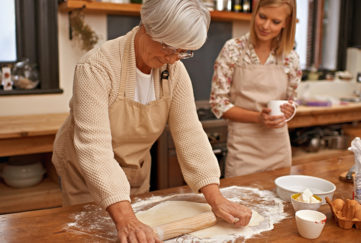 A mature mother and adult daughter baking together
