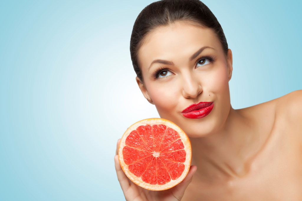 A creative portrait of a beautiful girl holding a fresh ripe grapefruit.