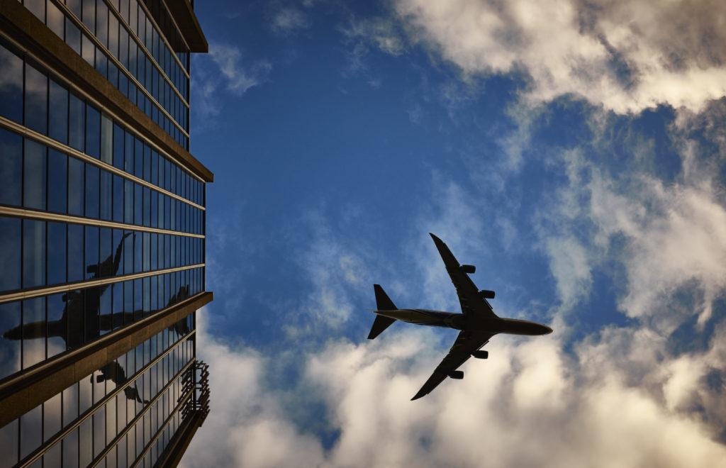 Plane flying over skyscrapers