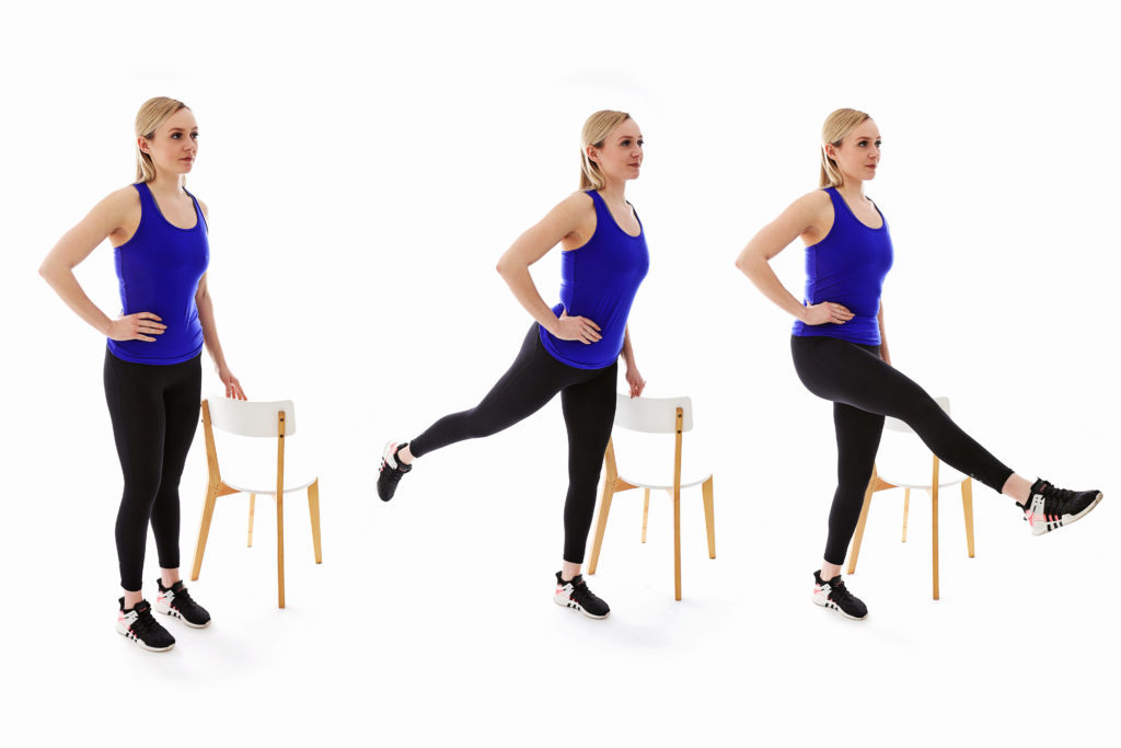 3 women doing leg rotations with chairs