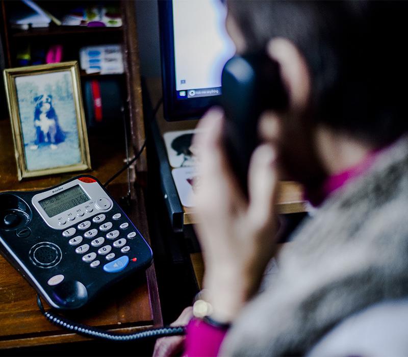 pet bereavement volunteer on the phone, back view