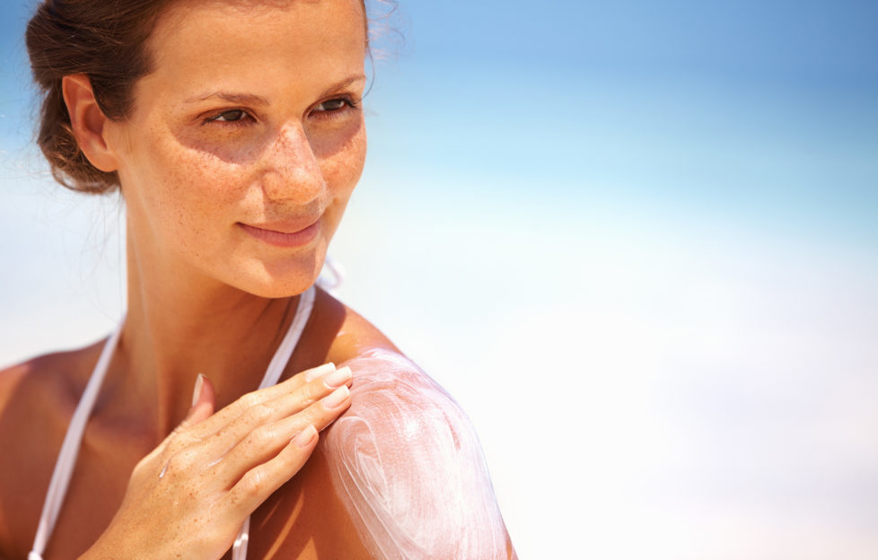 Closeup of lovely young woman applying sunscreen lotion on body