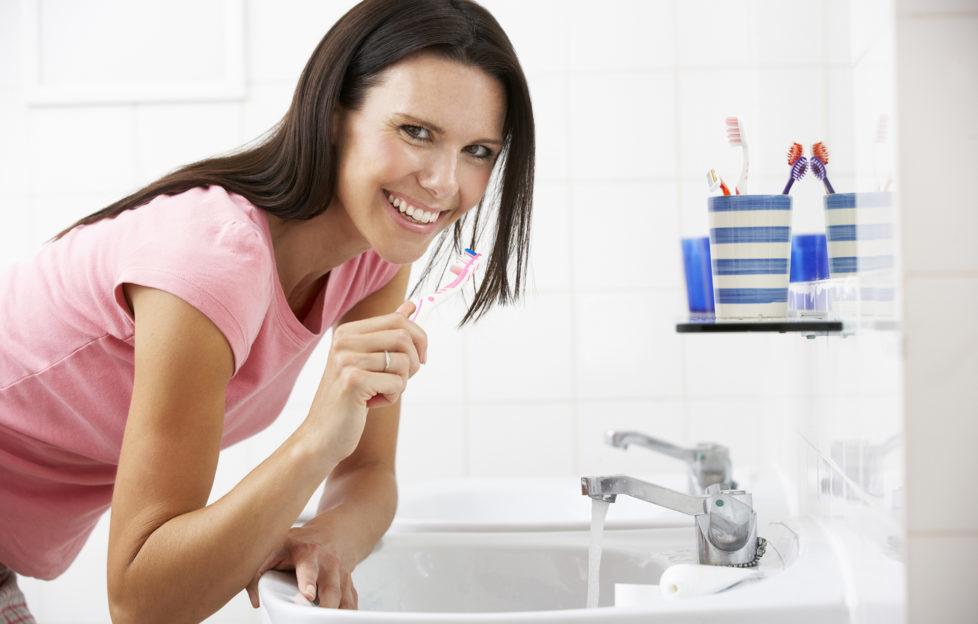 Woman In Bathroom Brushing Teeth Smiling At Camera