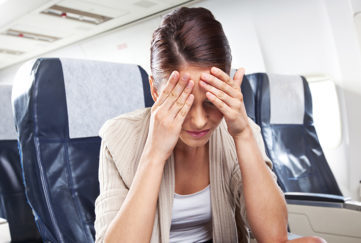 A young woman sitting on an airplane and suffering from headache.