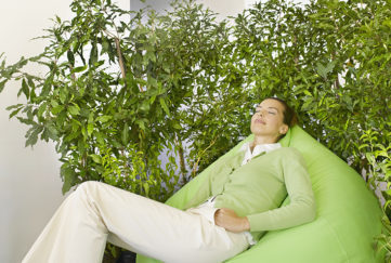 Businesswoman on beanbag surrounded by plants