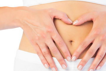 Close up picture of fit woman holding her belly