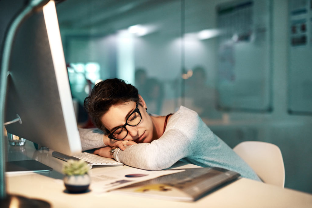 Shot of a young businesswoman sleeping on her desk at the office