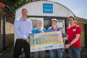 Magnus receiving a cheque from the People's Postcode Lottery presenter, along with two winners from the lottery Pic: Chris Watt