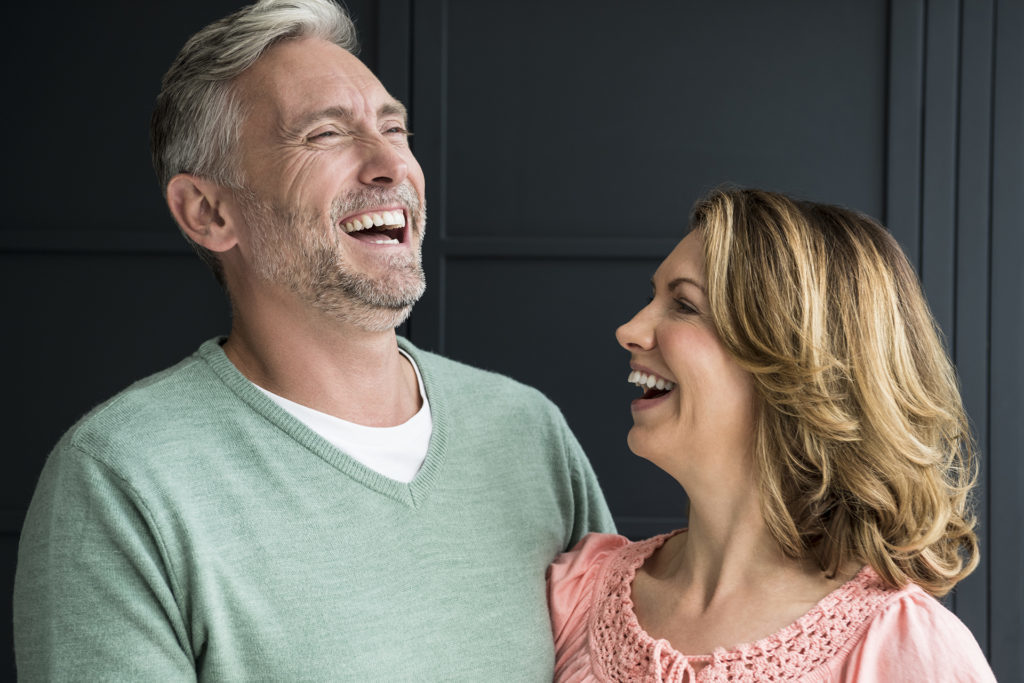Mature couple smiling and laughing in front of dark blue panelling
