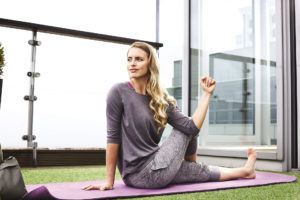 yoga pose 3, woman sitting on mat pushing straight right leg up and across body; fitness c;lothing