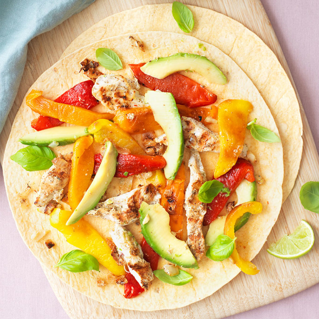 Chicken and avocado fajitas, open wrap seen from above scattered with chicken, red pepper, avocado etc