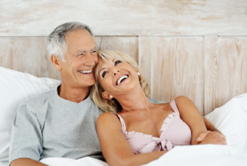 Portrait of a joyful mature couple smiling together in bed