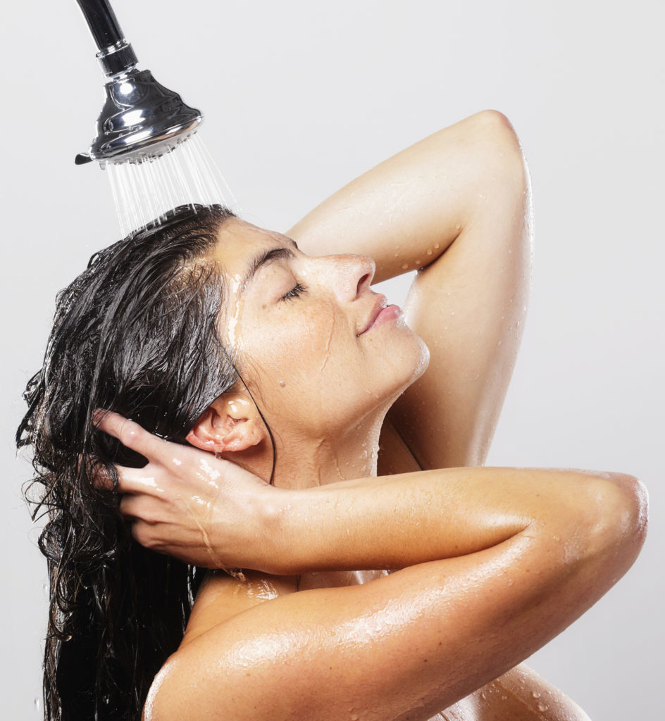 A dark-haired woman standing in a shower.