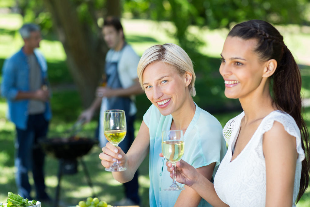 Ladies enjoying a glass of white wine at a barbecue Pic: Istockphoto