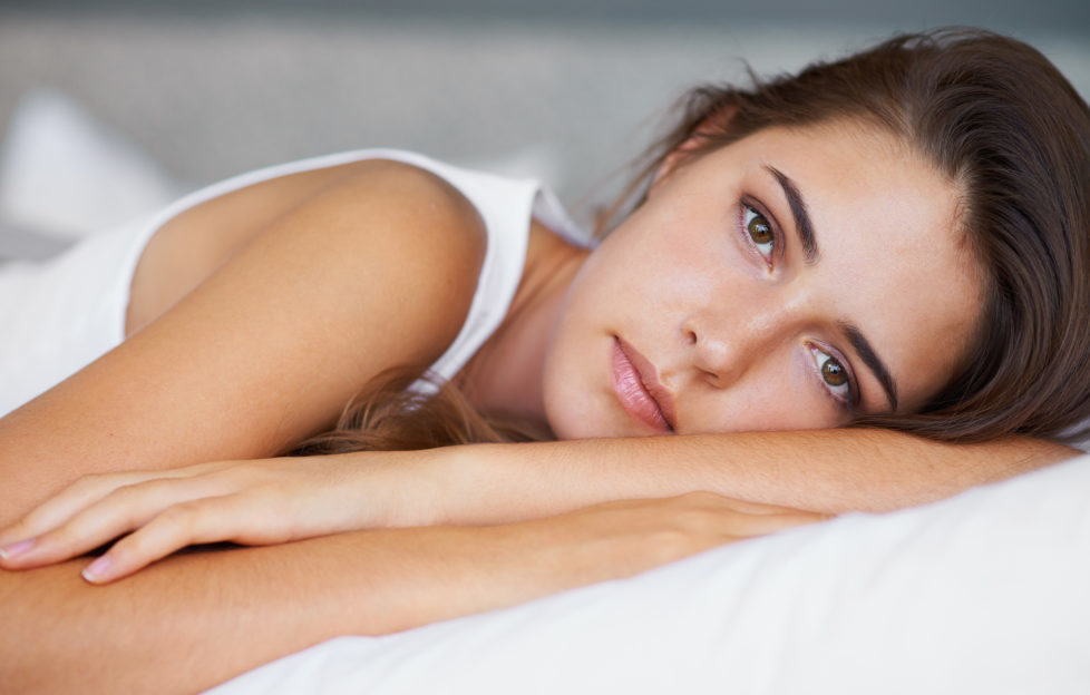 A beautiful young woman looking sad while lying on her bed