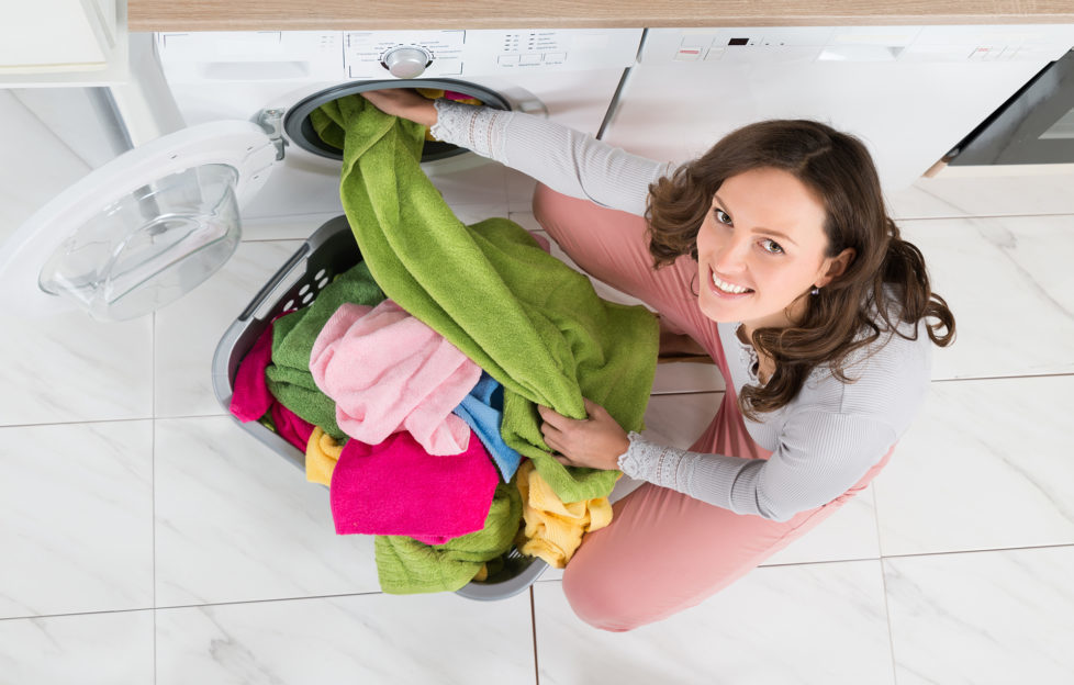 High Angle View Of Young Woman Loading Multi-colored Clothes In Washer