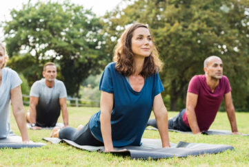 "Mature healthy people doing yoga at park. Group of multiethnic people exercising on green grass with yoga mat. Happy men and smiling women in yoga class doing exercise outdoor.""r"