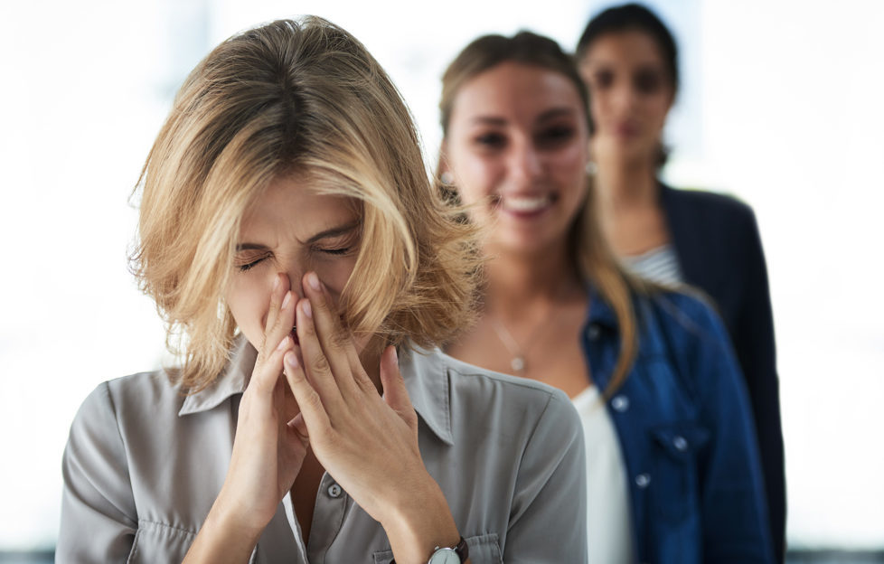 Woman sneezing as women behind her smile