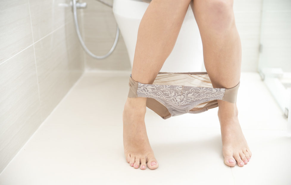 Close-up of legs and panties of young Caucasian woman sitting on toilet bowl.