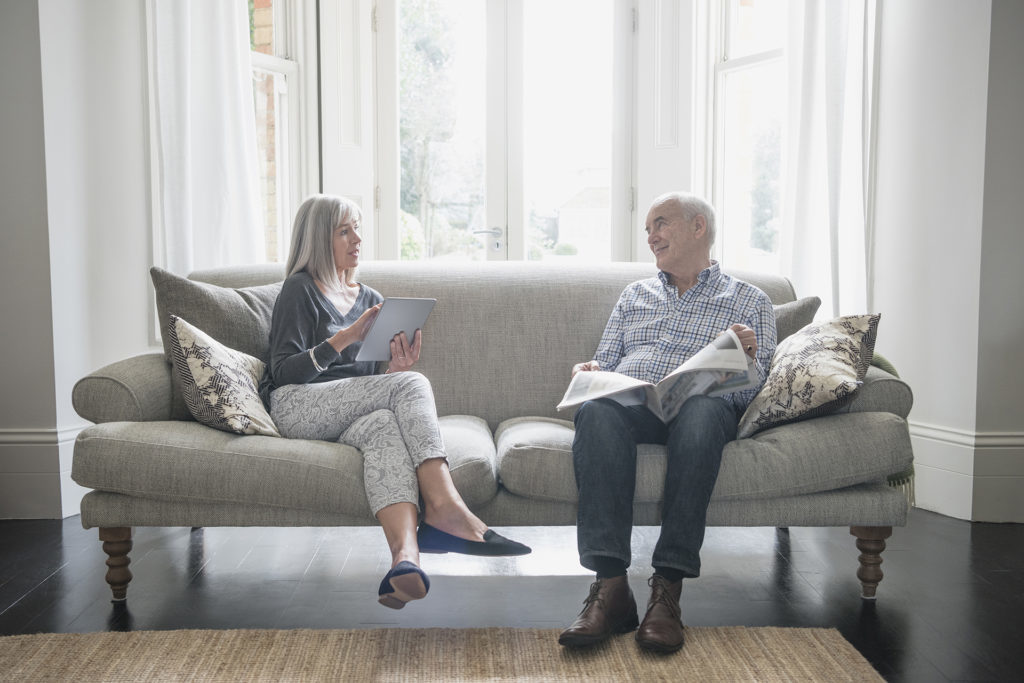 Senior women using digital tablet siting next to her husband on the sofa. He is reading the newspaper, and they are having a conversation together.