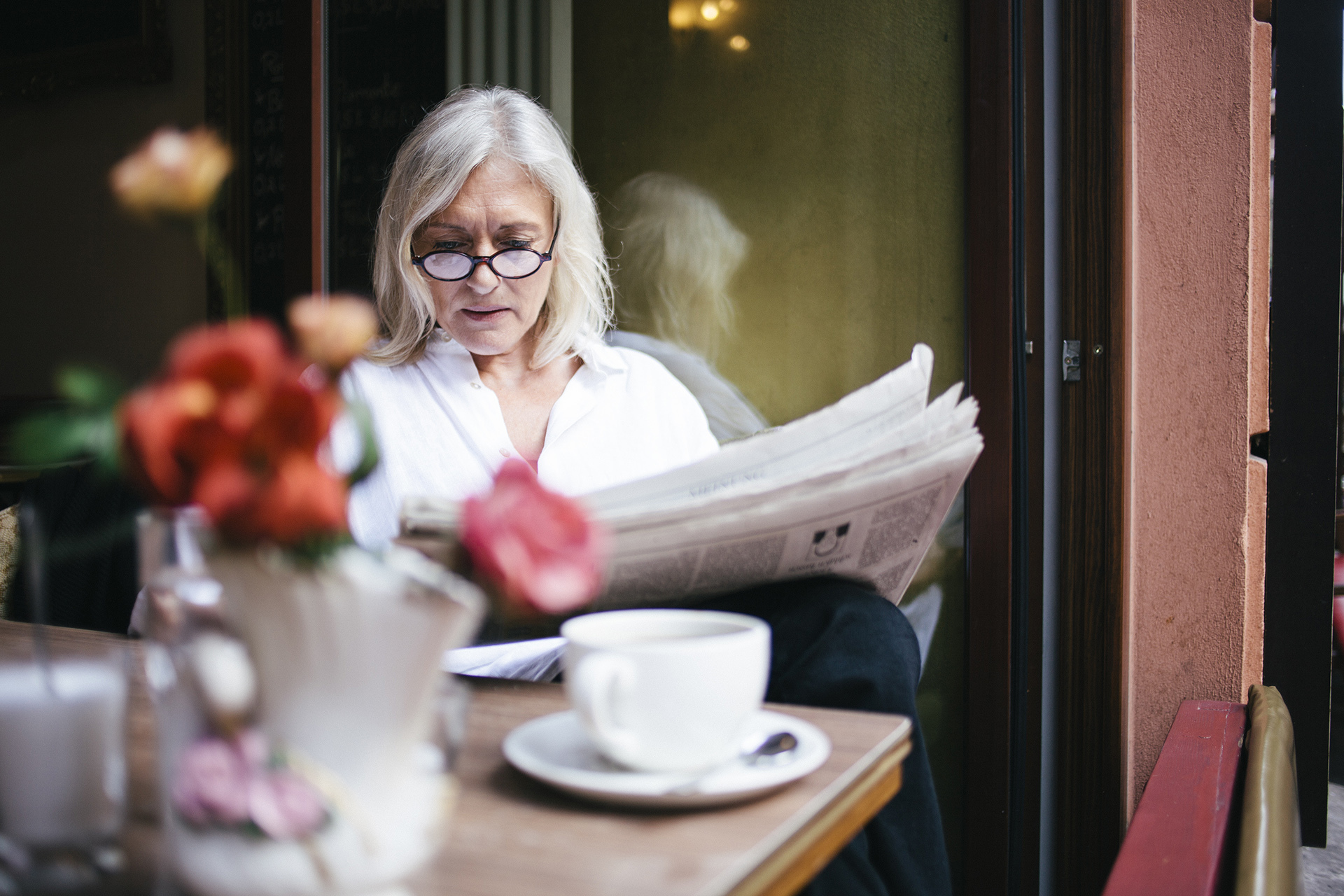 senior woman sits in a Sidewalk Cafe at an open window and reads a newspaper