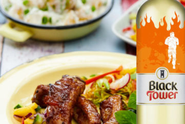 A bottle of Black Tower White wine and sticky ribs on a plate