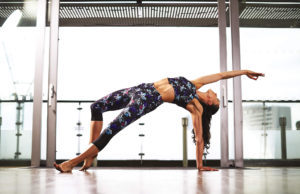 yoga pose 2, woman arched backwards balancing on one hand and one foot, fitness clothing