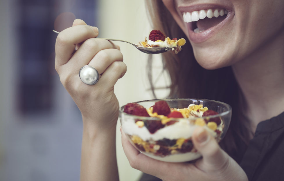 Young woman is eating breakfast cereal