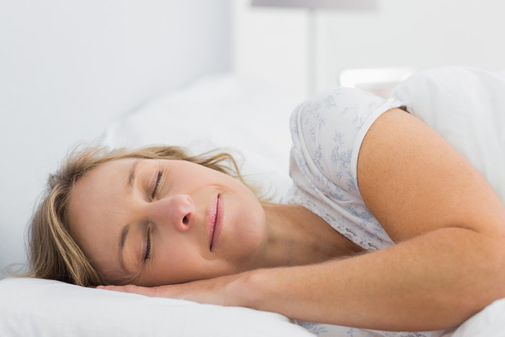 Peaceful blonde woman sleeping in bed at home in bedroom
