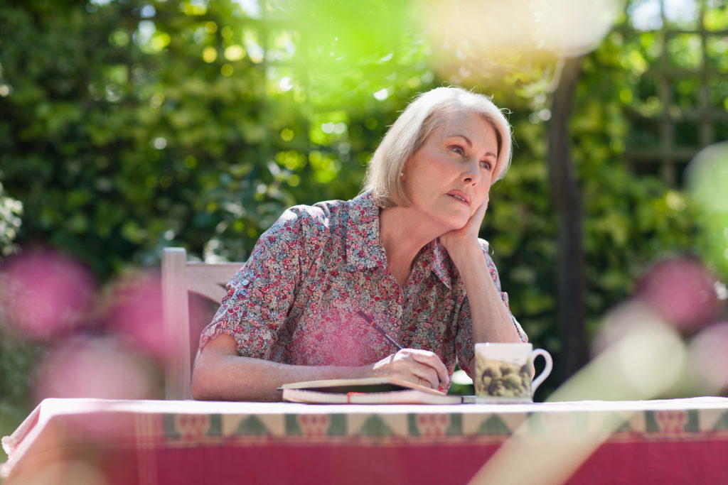 Pensive woman writing in journal at patio table