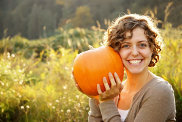 Smiling curly-haired girl holding a pumpkin to her cheek.