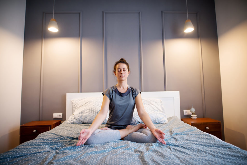 Front view of peaceful attractive middle aged active woman practising yoga on the bed