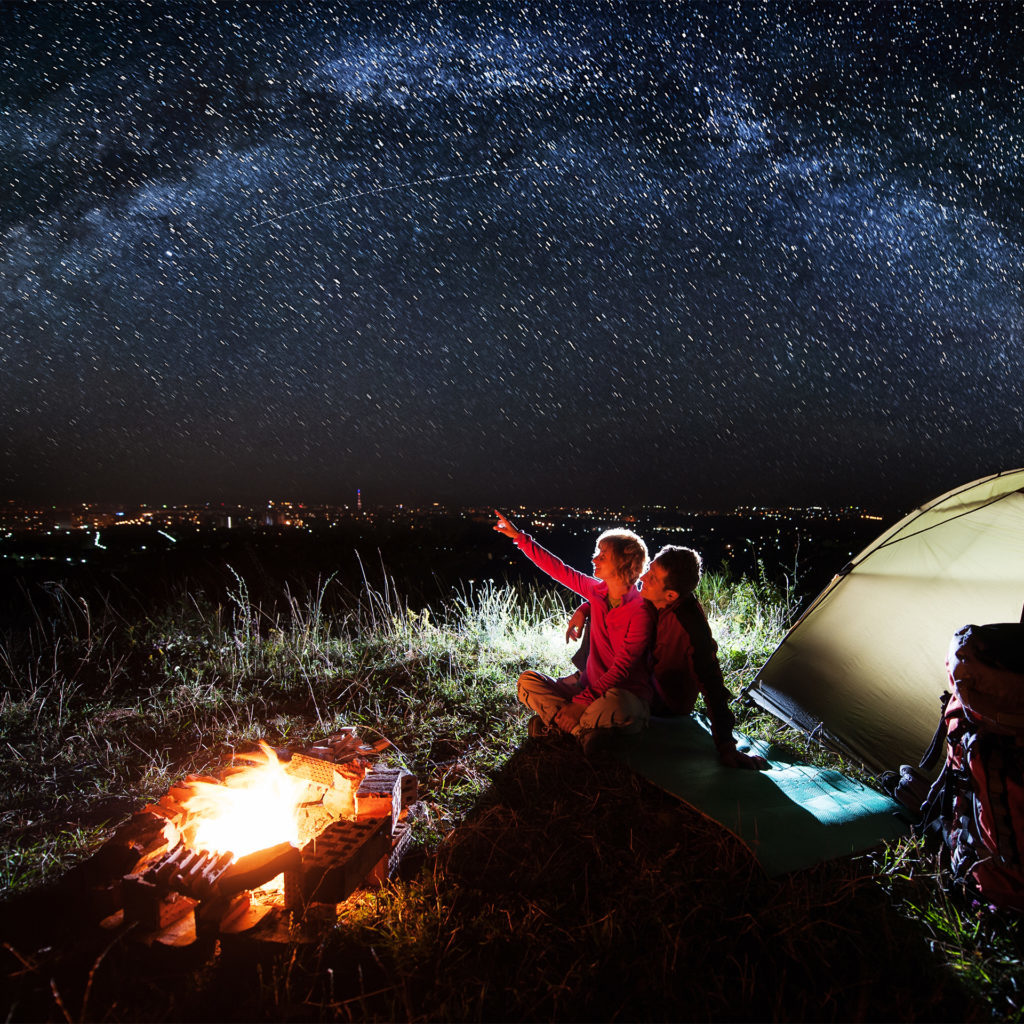 Night camping near the town. Young couple sitting near campfire and tent, looking at beautiful night sky full of stars.