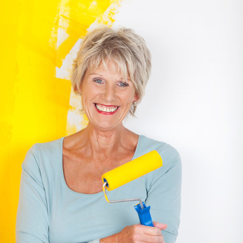 Smiling mature woman with paint roller, wall behind her is half painted yellow