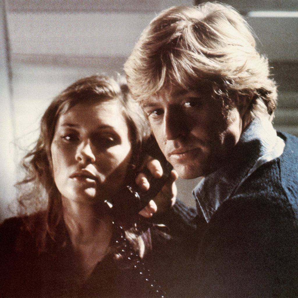 Robert Redford in Three Days Of The Condor with Faye Dunaway, he is holding a black phone receiver to her earand both look tense