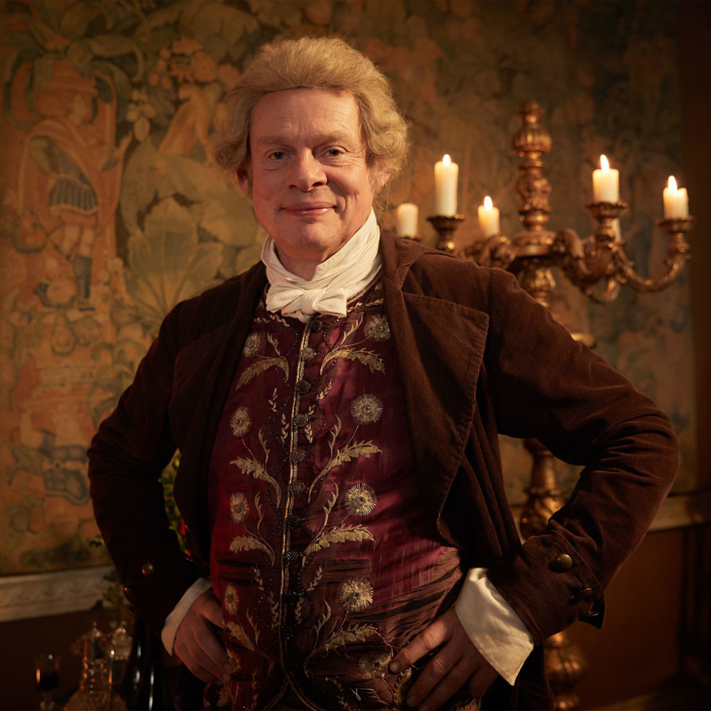 Martin Clunes, smiling, in wig and brocade waistcoat as Sir Pitt Crawley in ITV's Vanity Fair