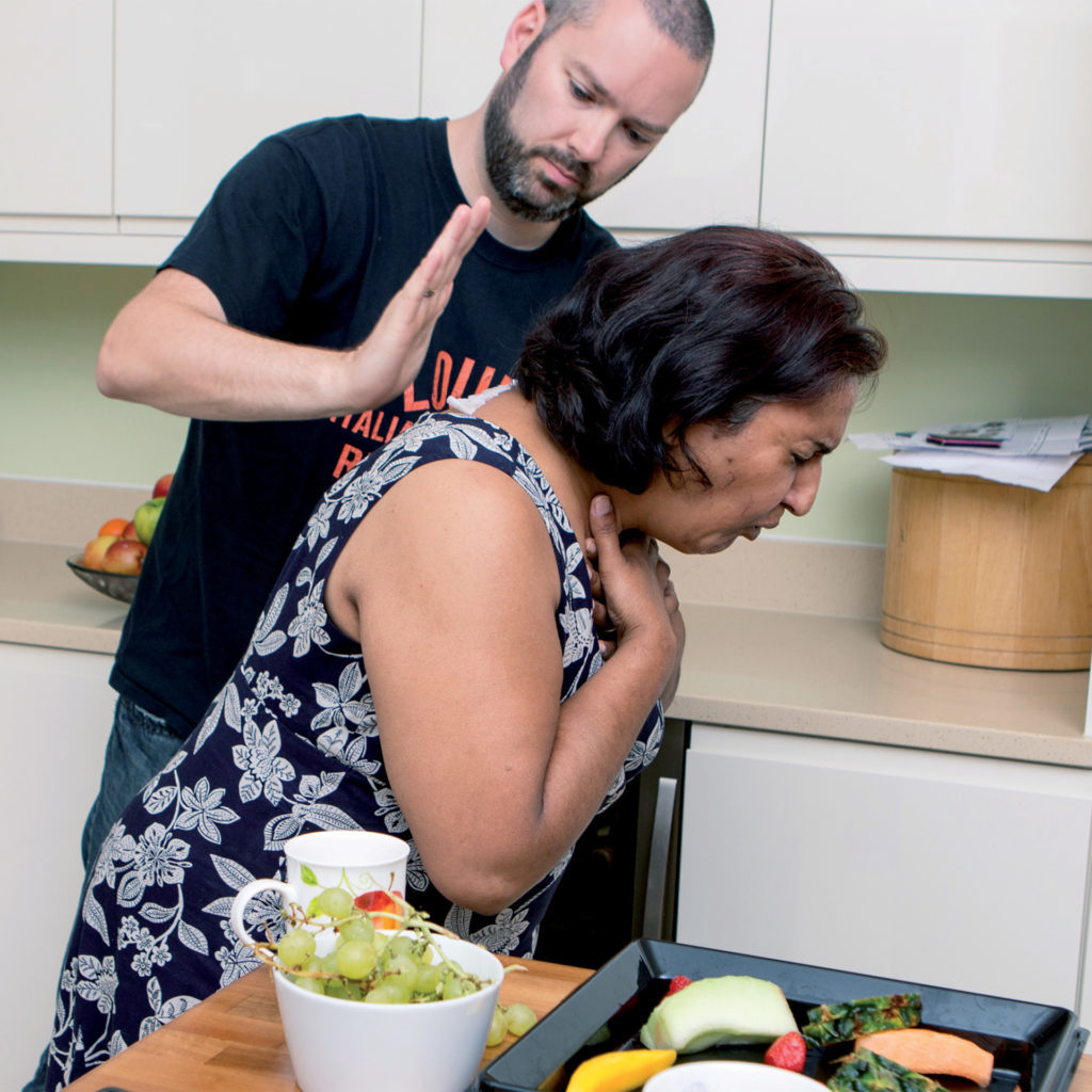 Woman in kitchen choking , man about to hit her on the back