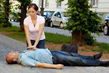 Middle aged man lying in tree lined street, woman doing chest compressions