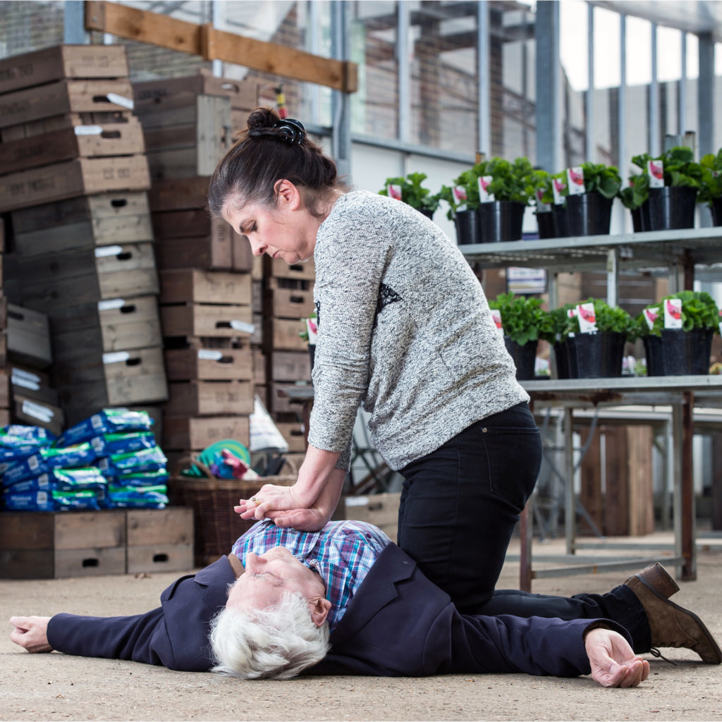 Older couple in garden centre, man lying on ground, woman performing chest compressions