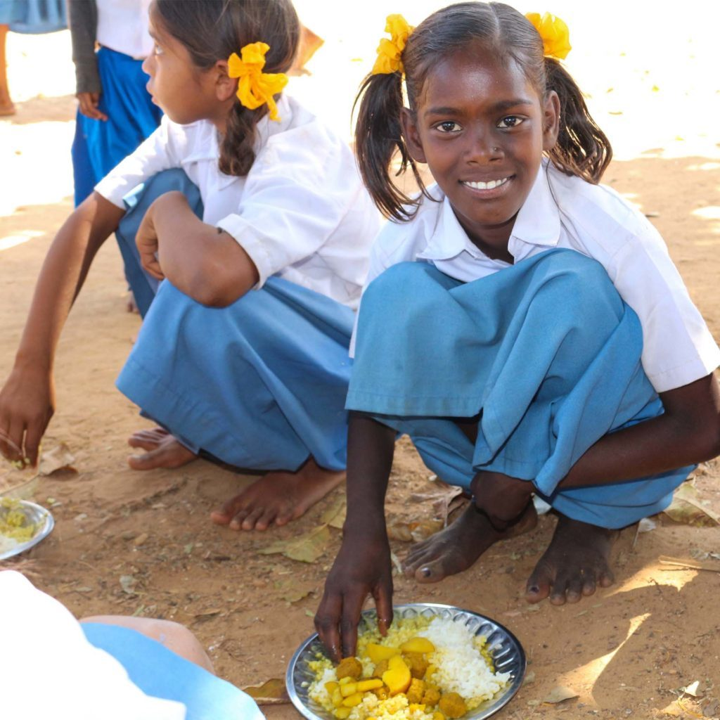 Smiling Indian schoolgirls crouched on ground about to eat plate of rice and vegetables