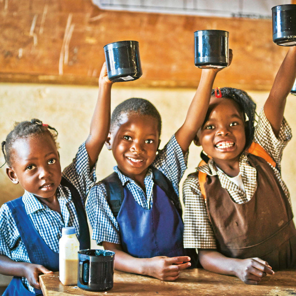 Three African schoolgirls at a table, smiling and holding up large tin mugs