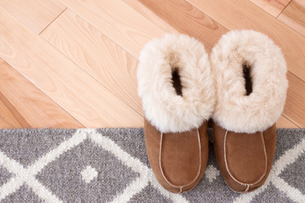 Gray rug and warm slippers on wooden floor.