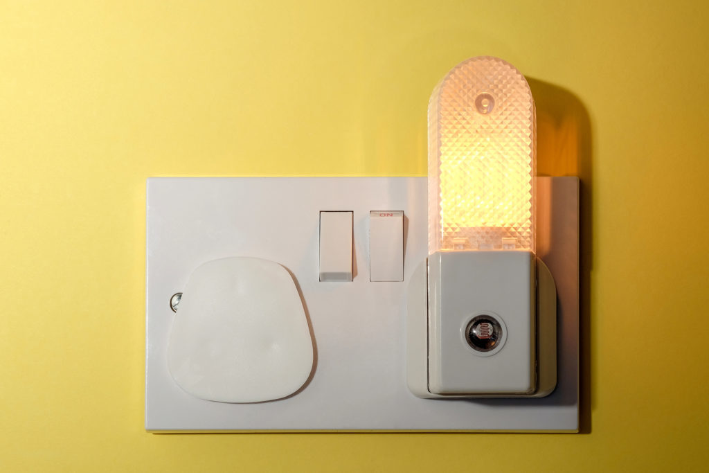 A child's nursery bedroom nightlight plugged in to wall socket with a safety cap fitted to the other unused socket