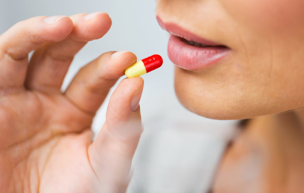 close up of woman taking medicine in pill