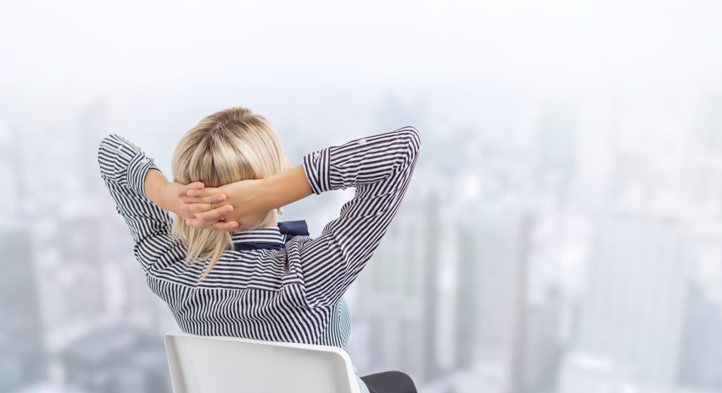 Business woman sitting in chair and day dreaming with city's skyline in background