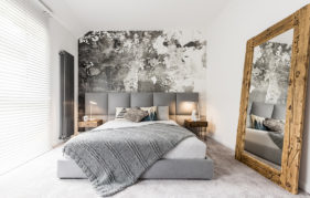 King-size bed with gray square headboard, large rustic wooden mirror and textured wall in trendy minimalist apartment Pic: Istockphoto