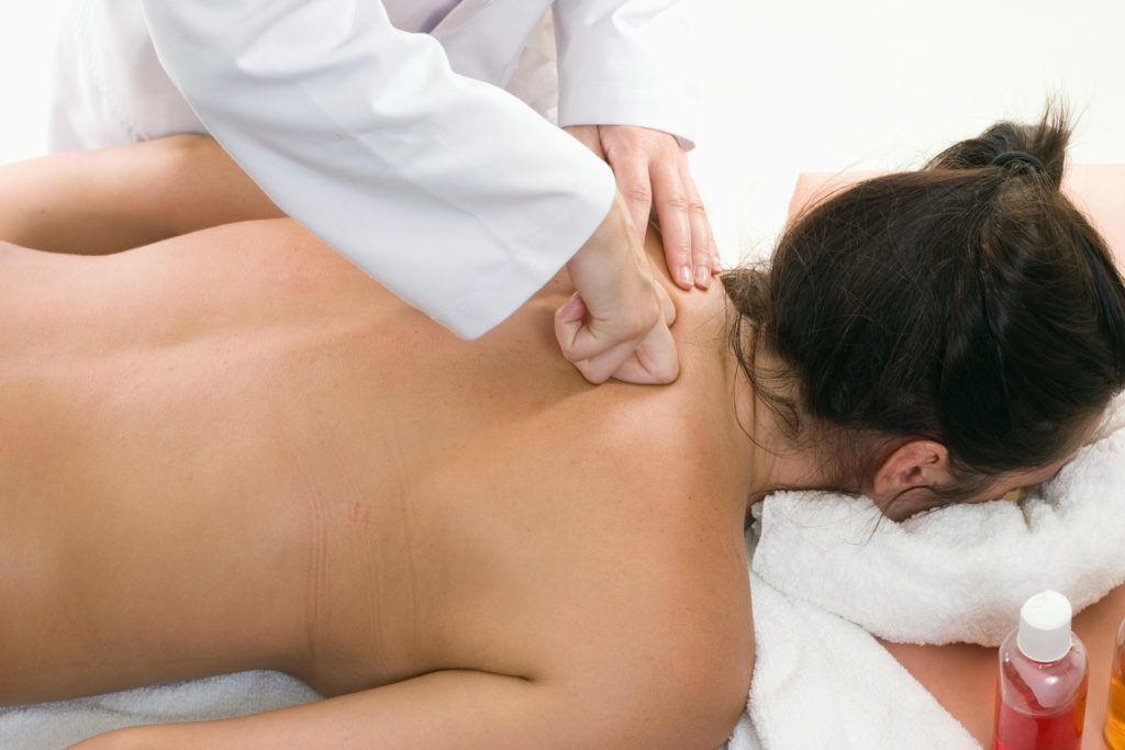 A woman receives a deep tissue massage with kneading.  Kneading is a massage technique in the category of petrissage movements