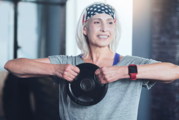 Getting stronger. Happy woman smiling while lifting a weight disk while doing swing exercise while having a training session indoors.