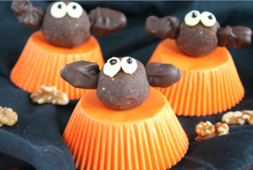 Bat shaped energy bites sitting on orange upturned cupcakes