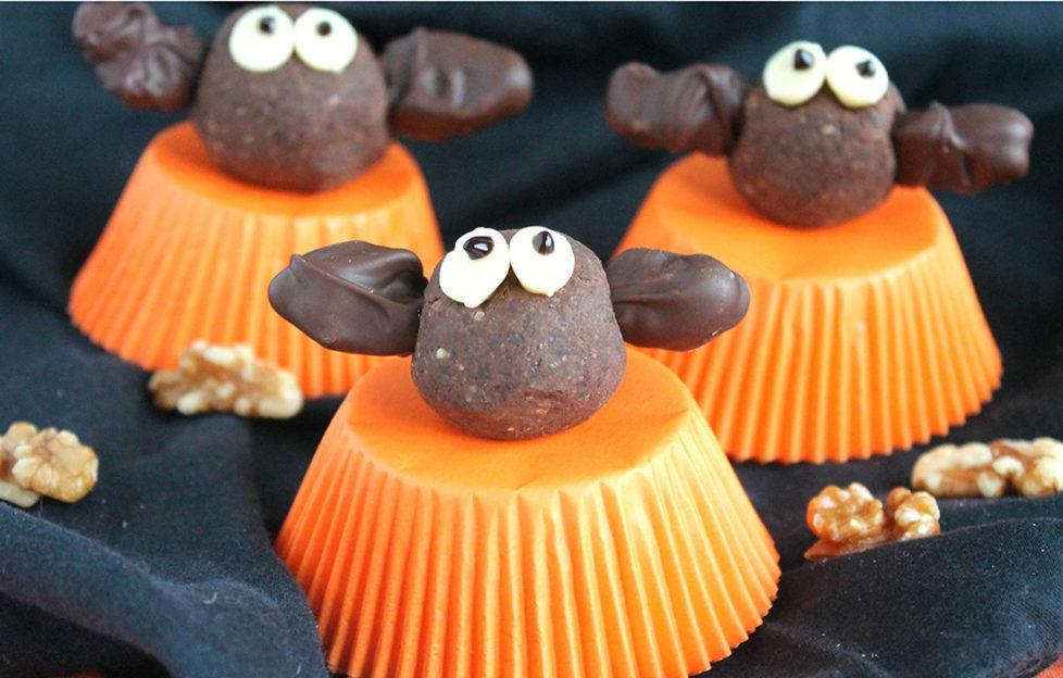 Bat shaped energy bites sitting on orange upturned cupcakes